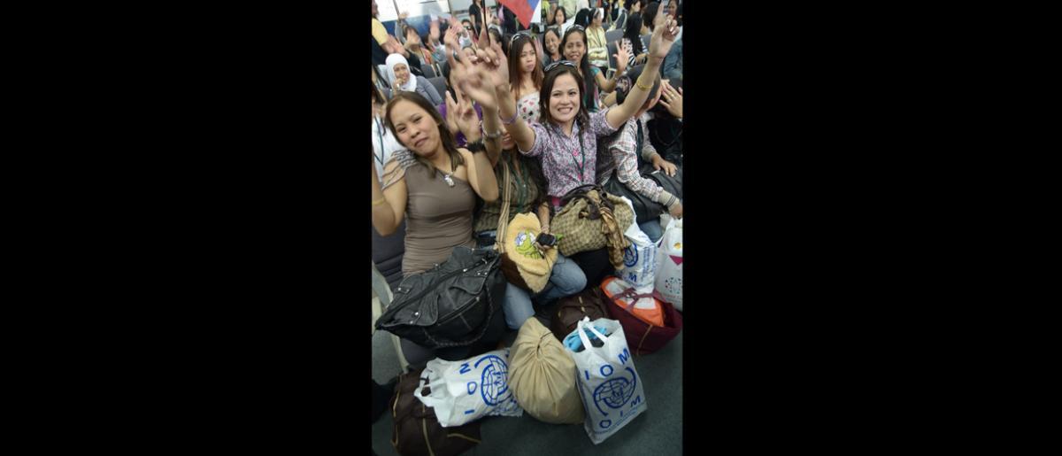Jay Alvarado (derecha), de la OIM, entrevista a una mujer retornada a Manila.  El 11 de septiembre, los nacionales filipinos partieron de Damasco (Siria), a bordo de un vuelo fletado por la OIM. © OIM 2012 (Foto: Ray Leyesa)