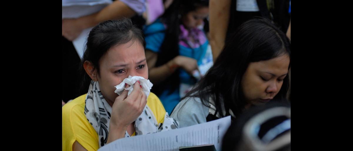 Filipinos fill out the necessary forms after arriving in Manila from Damascus, Syria on 11 September. © IOM 2012 (Photo: Ray Leyesa)