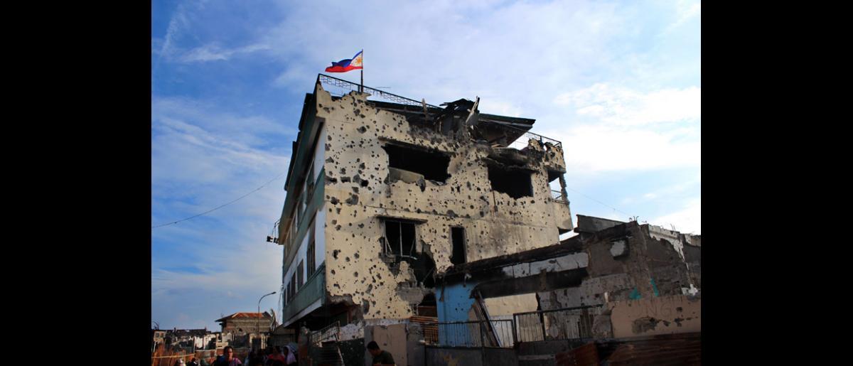 La bandera nacional de Filipinas ondea en lo alto de un edificio en ruinas en Santa Catalina,  Zamboanga, escenario de los encarnizados enfrentamientos protagonizados por las fuerzas gubernamentales y los rebeldes del Frente Moro de Liberación Nacional, el pasado mes de septiembre. © OIM 2013 (Fotografía por Joe Lowry)