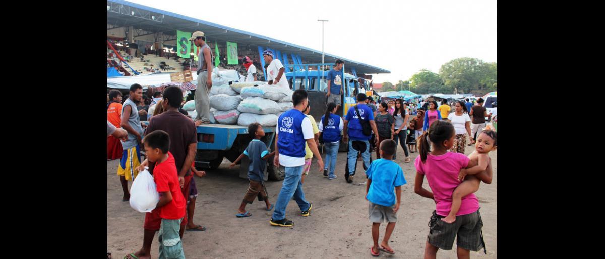 """Personal de la OIM dentro del Estadio Joaquin F. Enriquez Memorial (""""Grandstand""""), en la ciudad de Zamboanga, donde se hallan 21.000 desplazados. © OIM 2013 (Fotografía por Joe Lowry)"""