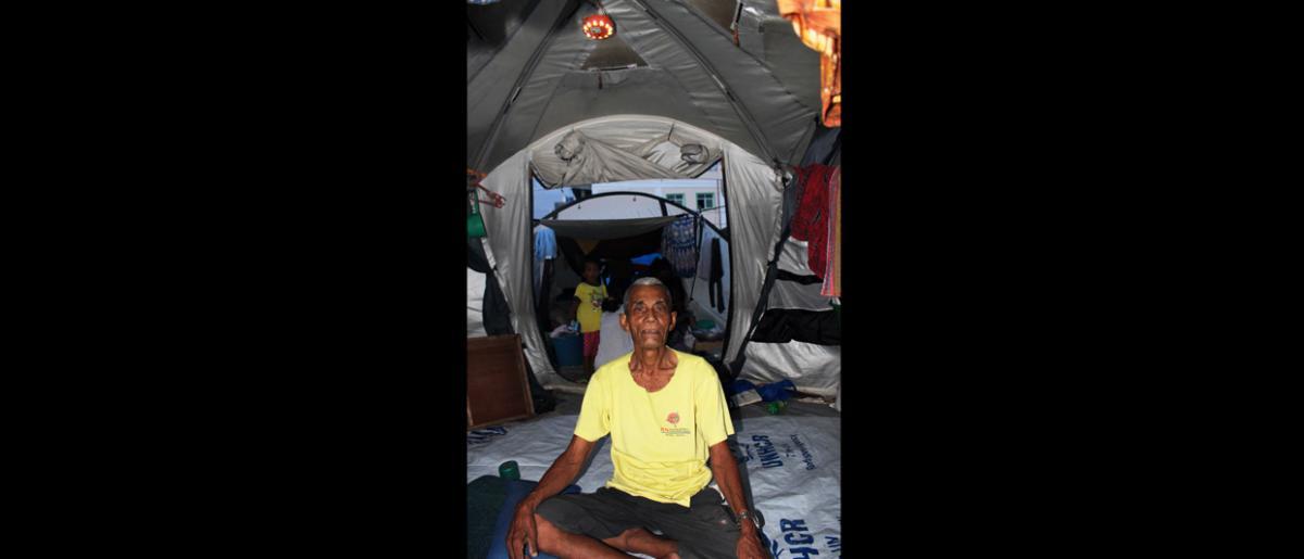 Un anciano  sentado bajo una lámpara solar donada por la OIM en un campamento improvisado en el frente marítimo de Cawa Cawa, en Zamboanga, al sur de Filipinas, donde dos meses después de los violentos enfrentamientos que paralizaron la ciudad sigue habiendo decenas de miles de desplazados. © OIM 2013 (Fotografía por Joe Lowry)