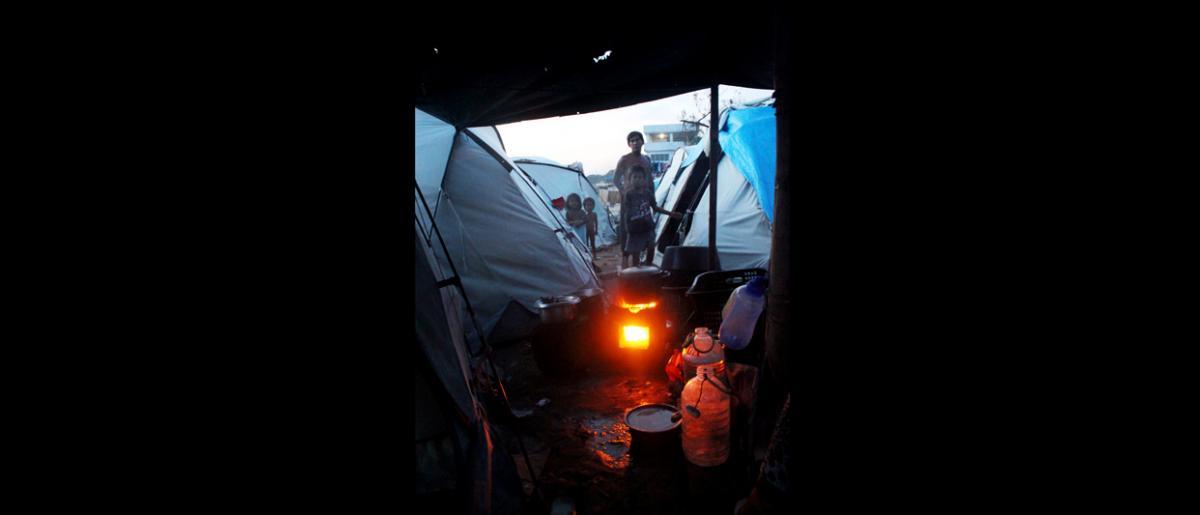 Cocinando en un fogón de carbón donado por la OIM en el frente marítimo de Cawa Cawa, en Zamboanga, al sur de Filipinas, donde sigue habiendo decenas de miles de desplazados tras los enfrentamientos entre el ejército filipino y el Frente Moro de Liberación Nacional del pasado mes de septiembre. © OIM 2013 (Fotografía por Joe Lowry)