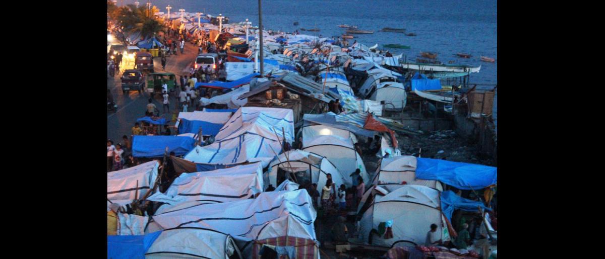 Campamento de desplazados en el frente marítimo de Cawa Cawa, Zamboanga, al amanecer. Miles de personas siguen desplazadas como consecuencia de los enfrentamientos protagonizados por el ejército filipino y el Frente Moro de Liberación Nacional el pasado mes de septiembre. © OIM 2013 (Fotografía por Joe Lowry)