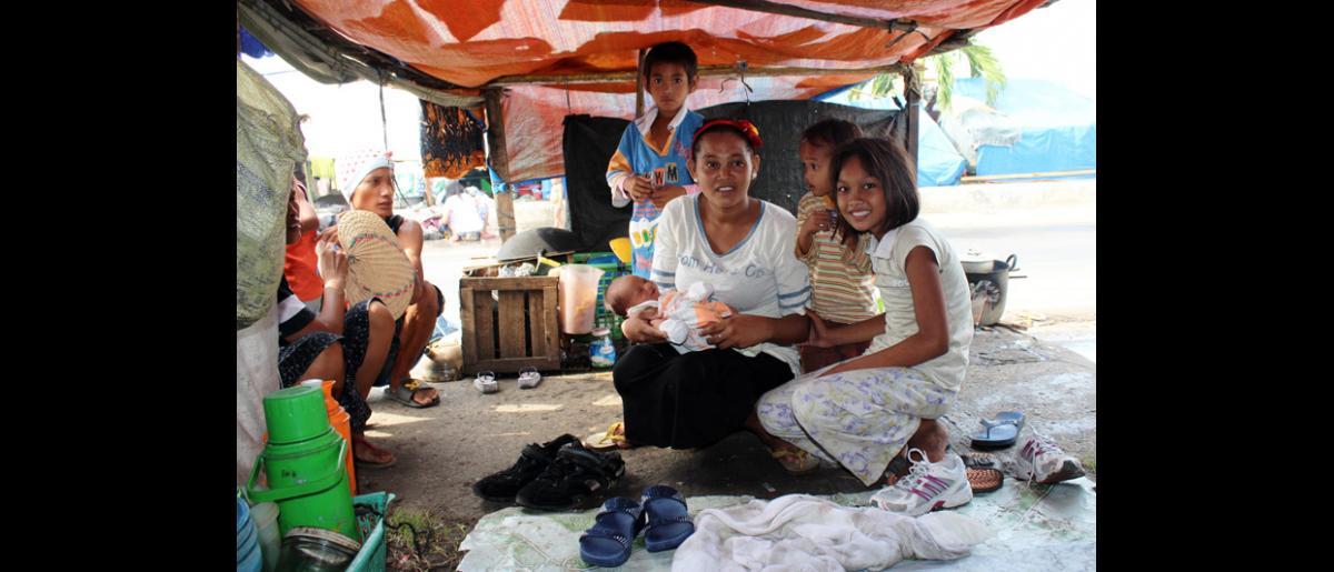 Misbah Gani con sus cuatro hijos, incluido Omal, que nació en este pequeño albergue situado al borde de la carretera en el frente marítimo de Cawa Cawa. La familia tuvo que huir de su hogar, en el suburbio de Mariki,  tras los encarnizados enfrentamientos entre el ejército filipino y el Frente Moro de Liberación Nacional.  © OIM 2013 (Fotografía por Joe Lowry)