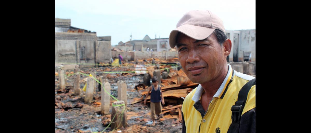"""Gapur Nasilin, de 46 años de edad, en las proximidades de las ruinas de su casa en el distrito Campo Muslim de Zamboanga. Afirma: """"No logro asimilar lo que ha ocurrido"""". Miles de vecinos de Río Hondo, un suburbio de Zamboanga, siguen viviendo en centros para desplazados tras los enfrentamientos que tuvieron lugar el pasado mes de septiembre entre el ejército filipino y los guerrilleros del Frente Moro de Liberación Nacional. © OIM 2013 (Fotografía por Joe Lowry)"""