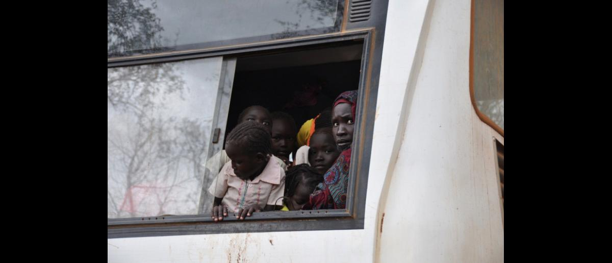 A woman and her children look out of the window of a bus as they arrive in Batil Refugee Camp. IOM assisted UNHCR with the relocation of 18,000 refugees from Kilo 18, a transit site kilometers from the border with Sudan. Refugees would walk for up to two weeks before crossing over into South Sudan in search of food, safety, and shelter. © IOM 2012