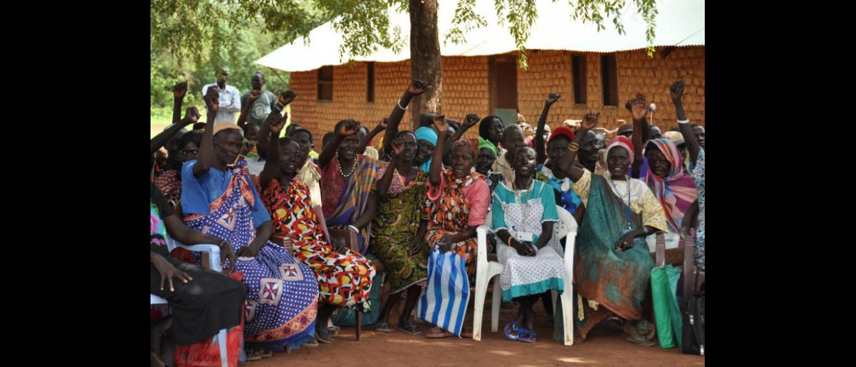 """Female ex-combatants raise their hands in solidarity as they shout, """"South Sudan Oye! South Sudan Oye!"""" DDR Day in Mapel, June 2012. © IOM 2012"""