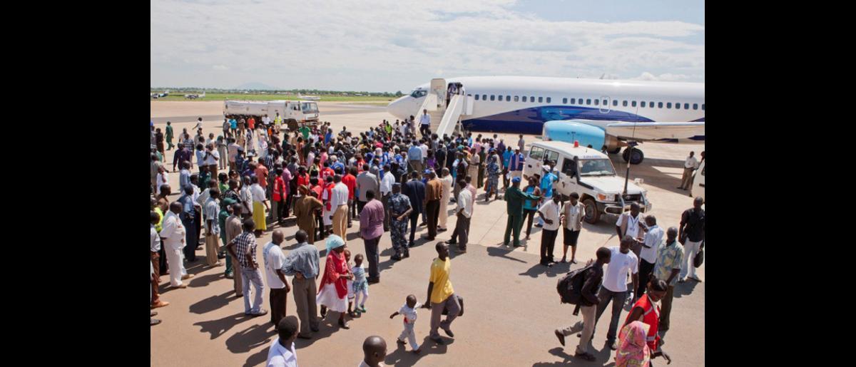 Los 326 sudaneses del sur, que han retornado desde Jartum hasta Juba a bordo de uno de los dos vuelos fletados por la OIM, reciben asistencia de la Organización.  Las personas cuyo destino final no es Juba son trasladadas al centro de tránsito del ACNUR, donde se les brinda alimentos y alojamiento. © OIM 2012 (Foto: Jasper Llanderal)