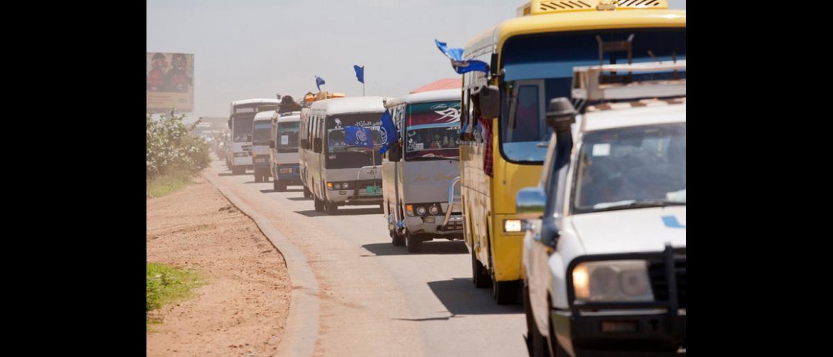 A leur arrivée, les rapatriés sud-soudanais embarquent à bord d'un convoi qui les transportera vers un centre de transit où ils recevront de la nourriture et un abri après avoir débarqué à l'aéroport international de Juba. © OIM 2012 (photo de Jasper Llanderal)