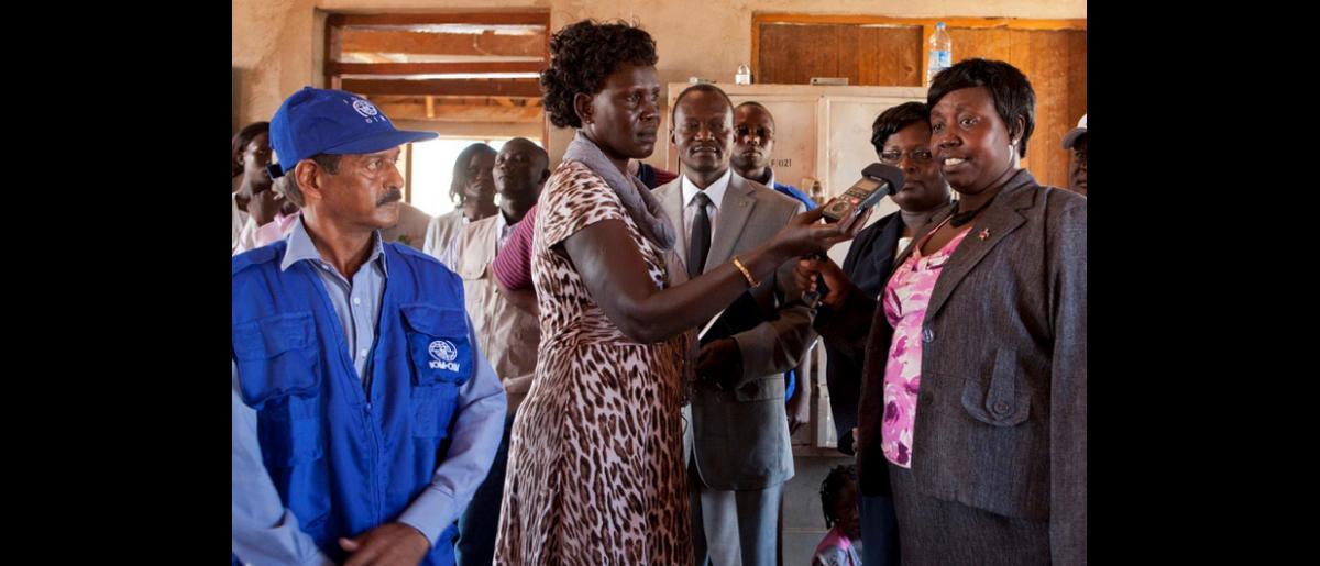 Los periodistas entrevistan a Sabina Dario Okolong (a la derecha), Viceministra de Asuntos Humanitarios y Gestión en Casos de Desastre, tras la llegada, el 14 de mayo, del primero de los dos vuelos fletados por la OIM, que ha realizado el trayecto Jartum-Juba con 326 pasajeros a bordo. © OIM 2012 (Foto: Jasper Llanderal)
