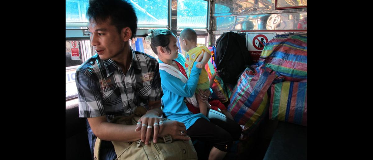 Ma Lay Lay (centre), the 100,000th refugee assisted to resettle by IOM Thailand in recent times with her son Ywar Mar Ser (11 months) on the bus leaving Mae La refugee camp. © IOM 2012