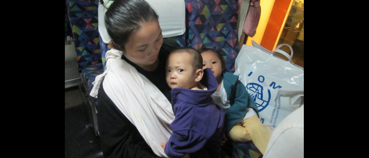 Ma Lay Lay, the 100,000th refugee assisted to resettle by IOM Thailand, and her children Labur Paw (3) and Ywar Mar Ser (11 months) on the bus before their early-morning flight from Bangkok International Airport. © IOM 2012