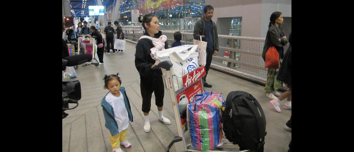 Ma Lay Lay, the 100,000th refugee assisted to resettle by IOM Thailand, and her children Labur Paw (3) and Ywar Mar Ser (11 months) at Bangkok International Airport prior to their early morning flight to the USA. © IOM 2012
