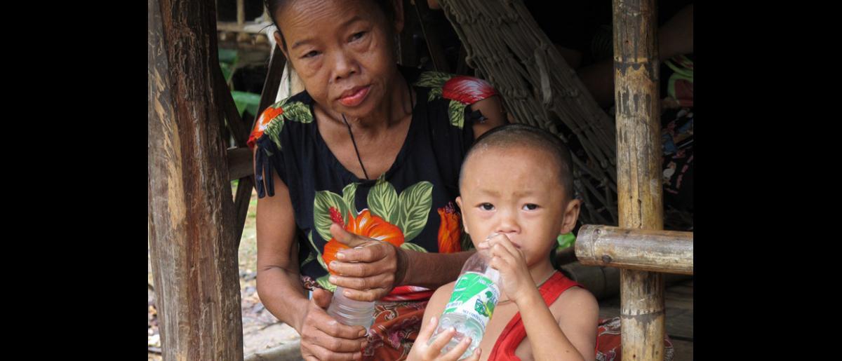 Un menor toma su medicina, quimioprofilaxis, diluida en agua. Así se previene el desarrollo de la enfermedad por contacto con un familiar que padezca tuberculosis activa. Fotografía tomada en un campamento para refugiados de Myanmar en Tailandia septentrional. © OIM 2012