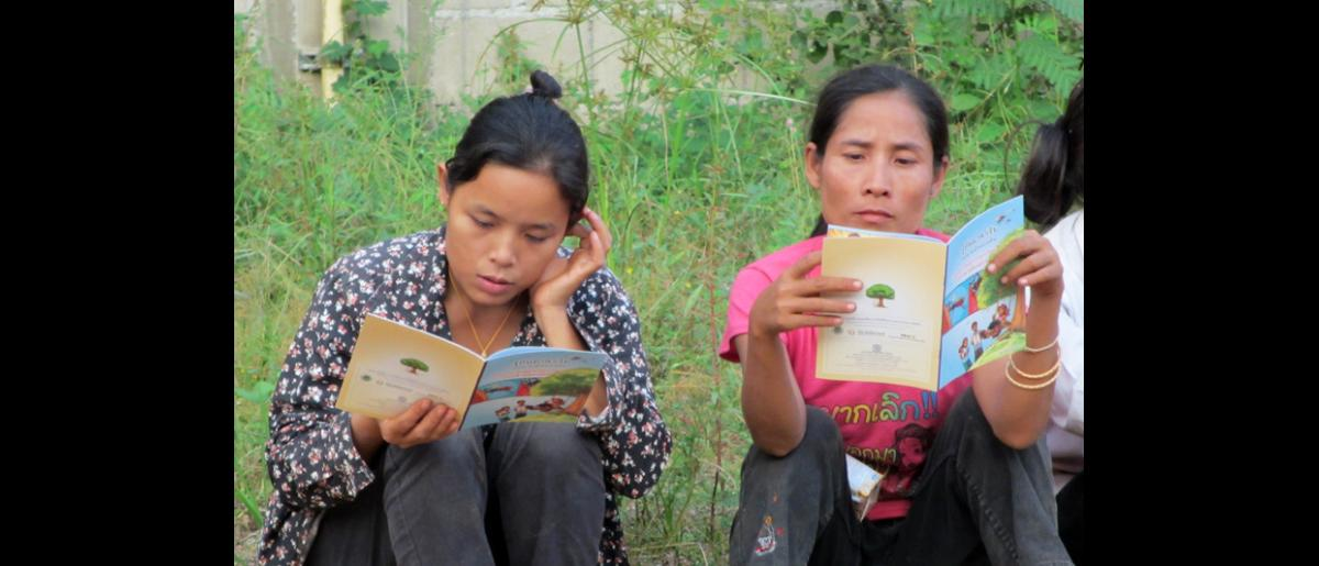 Migrant workers in Mae Hong Son read IOM comic book with malaria and personal protection messages. © IOM 2014