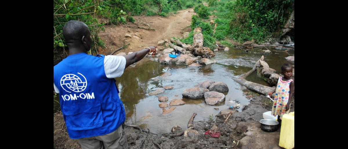 An IOM project officer points at an unsafe stream that some of the refugees get water from at the base of Kyangwali settlement in western Uganda. The ECHO funding will provide more safe water to the settlement. © Richard M Kavuma / UN Migration Agency (IOM) 2018
