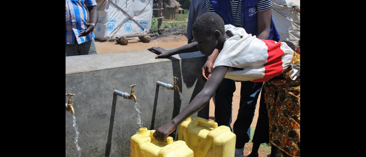 A girl draws water from a newly constructed piped water system funded by European Union humanitarian aid in Bidibidi refugee settlement, northern Uganda.  The EU has approved further funding for IOM to provide services to refugees in western Uganda and in the northern district of Moyo. © Abubaker Mayemba / UN Migration Agency (IOM) 2018