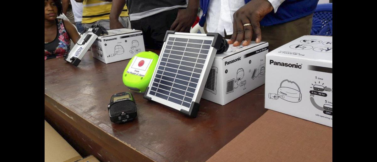 """Panasonic lanterns are especially bright and we can charge mobile phones with them too"". Community members are particularly happy with the lanterns' brightness and functionality. Sierra Leone. Photo: IOM"