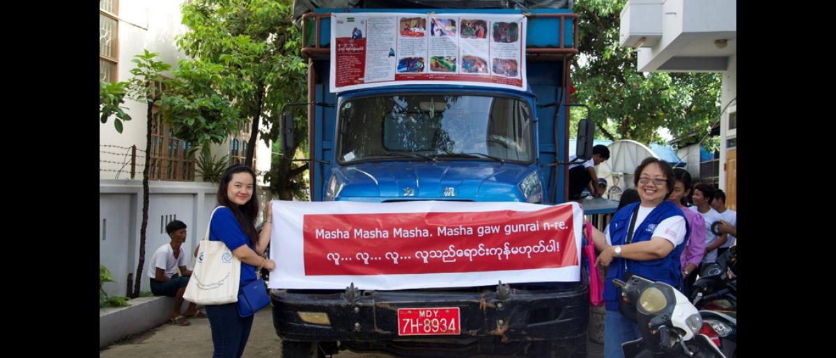 """IOM staff stretching a banner across a truck used for roadshows. The banner reads """"Humans..Humans….Humans… Human beings are not for sale"""" in Kachin and Burmese."""