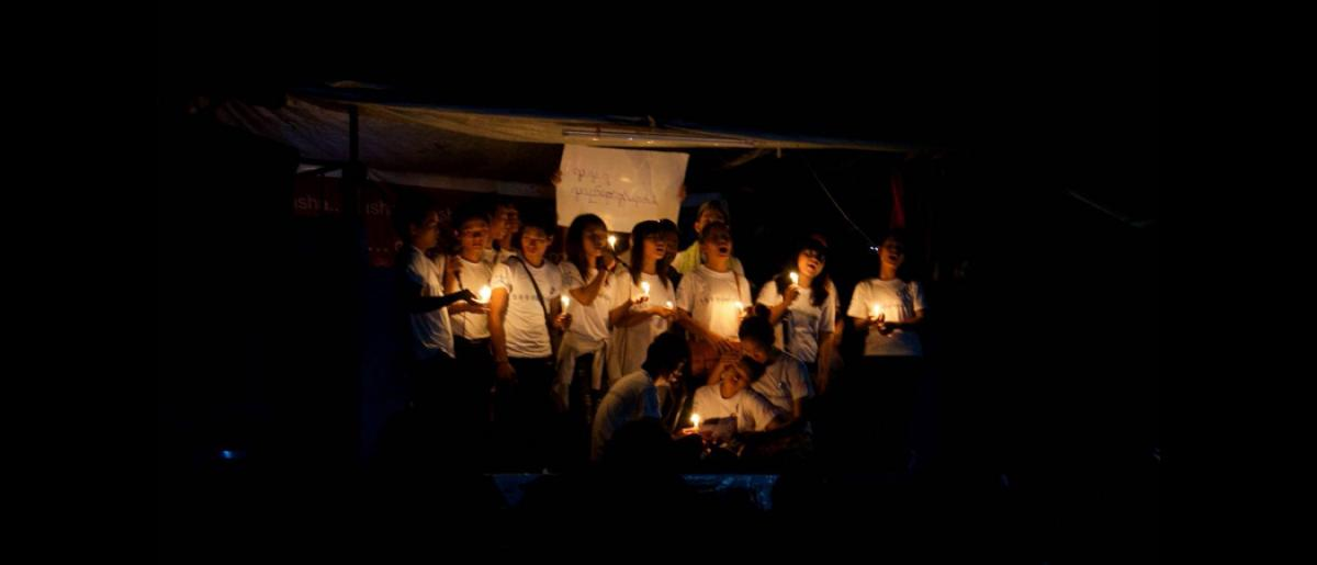 Youth volunteers performing with candles as part of a play at an evening session in an IDP camp.