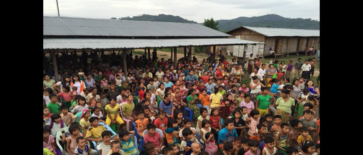 A large crowd of children, youth and women gather at an IDP camp to watch songs and plays performed by youth volunteers. A total of five songs and two plays in Kachin and Burmese were written for the information campaign.