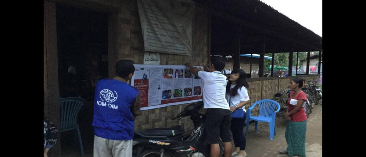 As part of the information campaign, posters containing information on human trafficking are put up in places with high human traffic in IDP camps. In this picture, an IOM staff puts up a poster outside a health clinic.