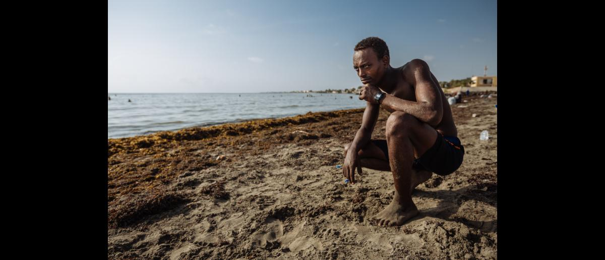 Obsa trains on his acrobatic moves on the beach in the morning. As an Ethiopian migrant, he came to Djibouti when he was a child looking for work.