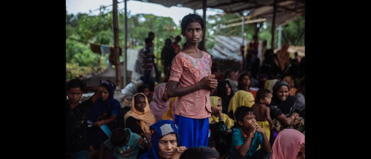 Rohingya refugees wait under shelter from the rain in the Kutupalong refugee camp in Bangladesh
