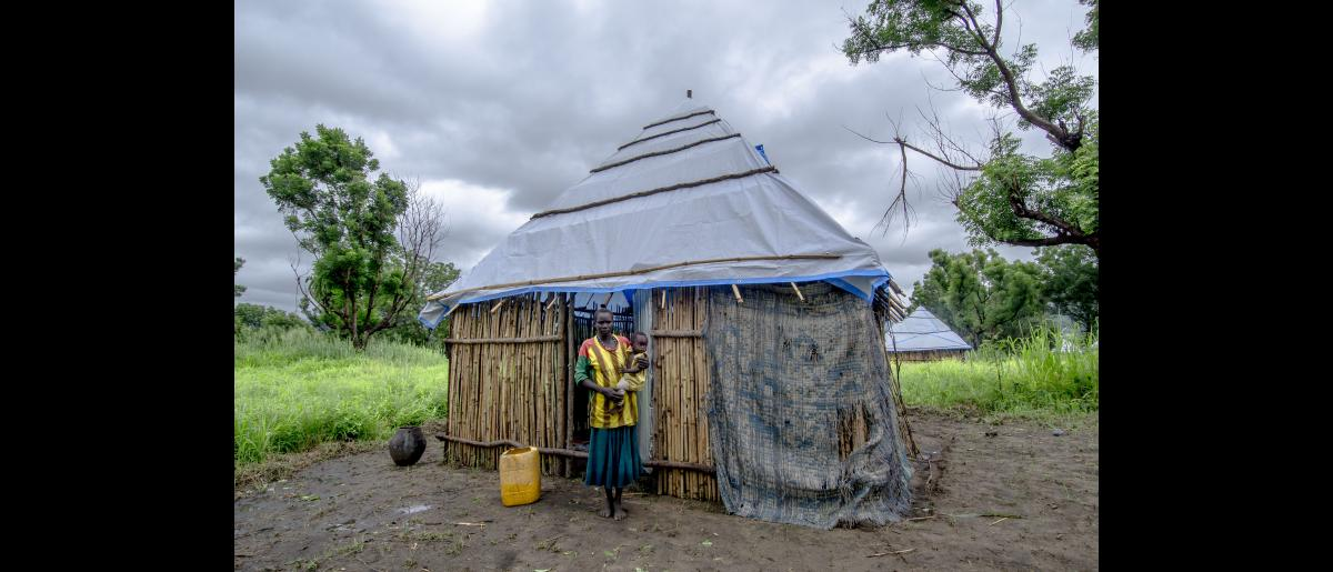Aboy, a widow with three children, with her son in front her home. She is a vulnerable host community member and beneficiary of transitional shelter who is now seeking funds to finance to finish final phase of constructing her home : mud plastering of walls.