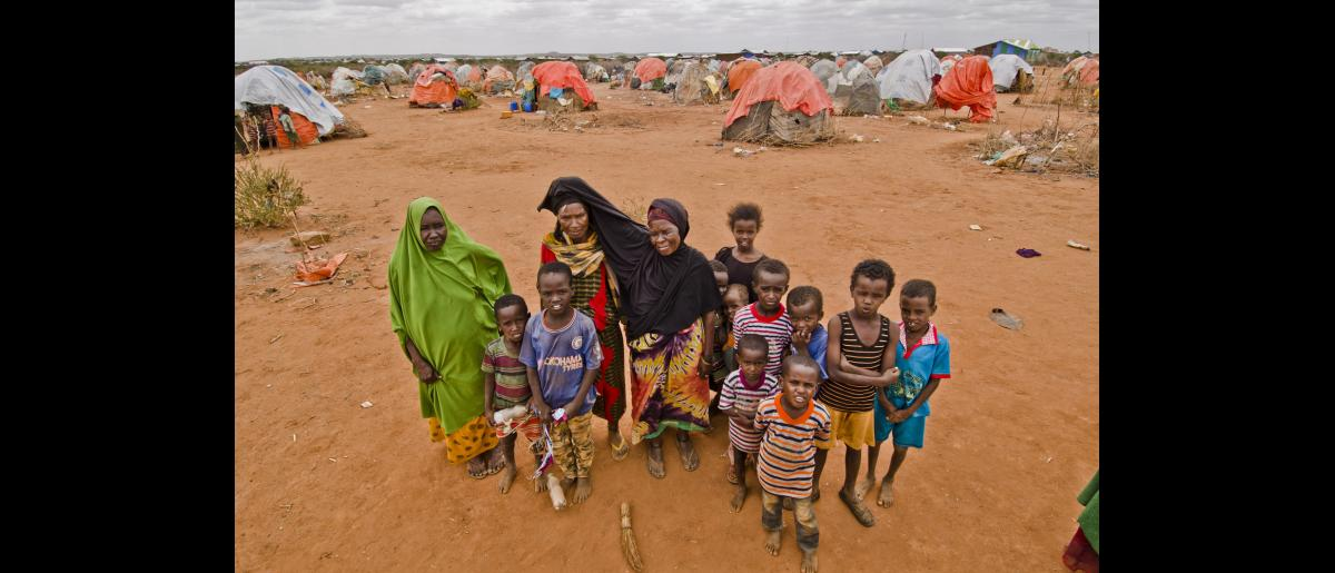 Displaced Somali women and children gather around and pose for the camera.