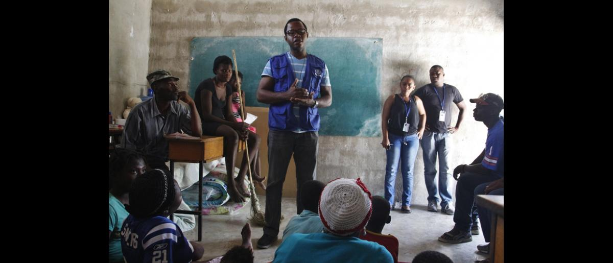 An IOM Protection staff talks with families hosted at the Fond Bayard school to explain the purpose of IOM's monitoring activities. © IOM/Ilaria Lanzoni 2015