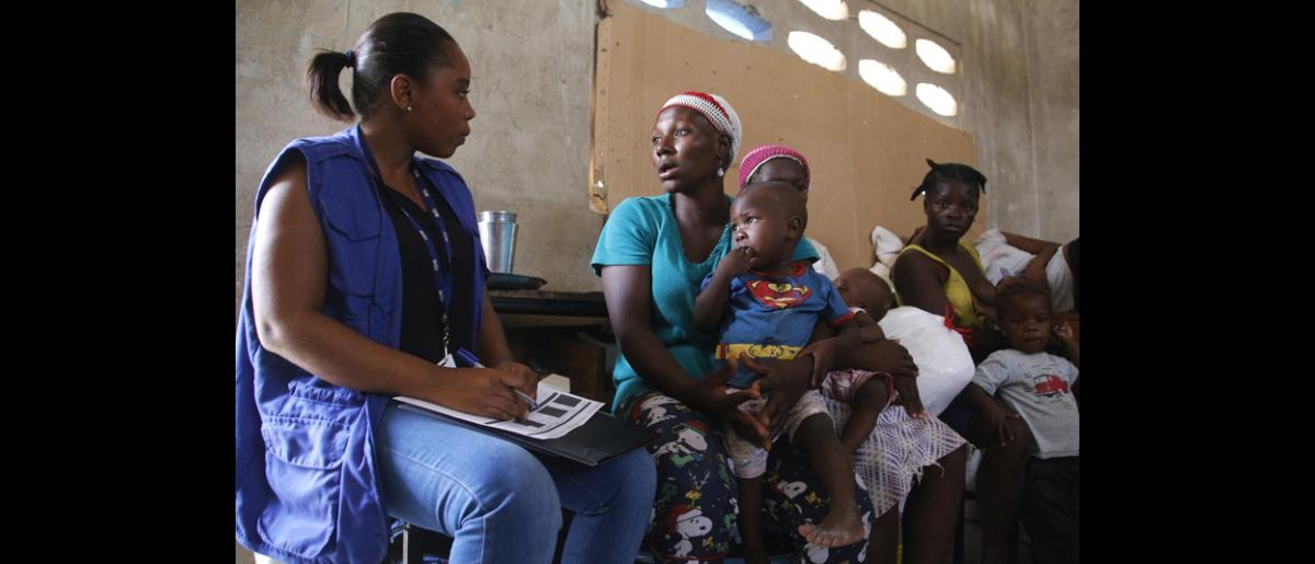 An IOM staff interviews families having recently crossed into Haiti from the Malpasse border crossing point. © IOM/Ilaria Lanzoni 2015