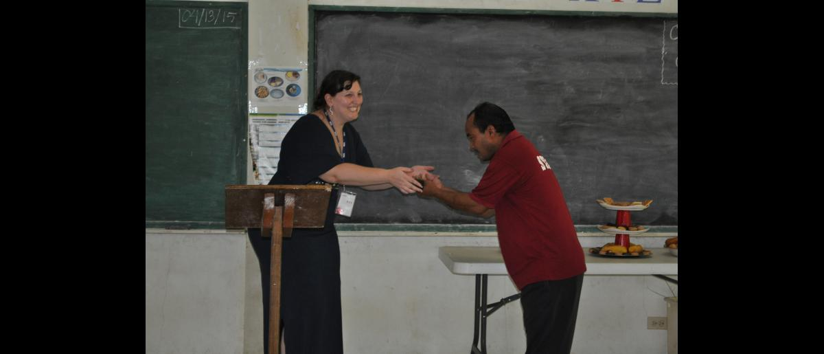 IOM's Kate McDermott ceremonially hands Principal Benjamin Saimon a rubber mallet (for maintenance of fire extinguishers) issued during the official handover ceremony of a 5,000 gallon rainwater and guttering system for Seinwar Elementary School, Pohnpei State.
