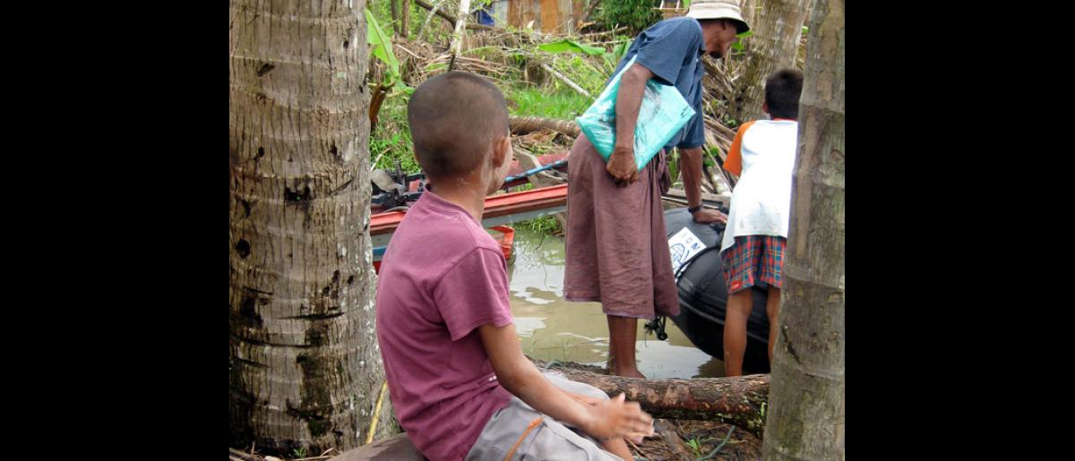 LOOKING ON. A boy watches from a short distance as some of his fellow villagers inspect a Zodiac boat which an IOM mobile team used to reach their village. Zodiac inflatable boats and other motorized boats are being used by IOM to bring in medical assistance and relief supplies to cyclone survivors in remote areas. © IOM 2008 - MMM0129