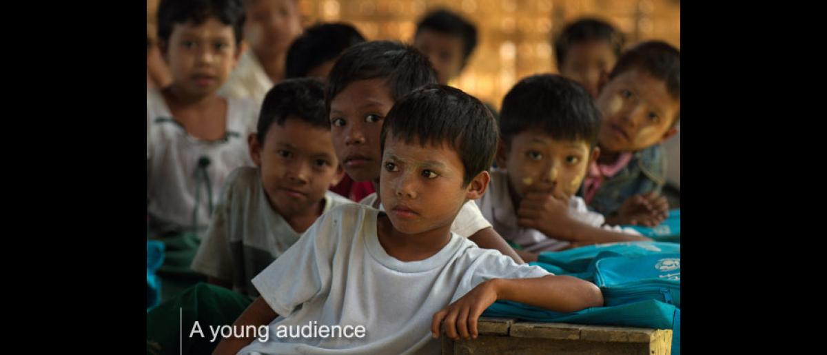 Children at Kyaung Su village school in Bogale Township listen to IOM staff explaining the reasons why they should take the deworming tablets that will be distributed to them. © IOM/Piers Benatar 2008 - MMM0387