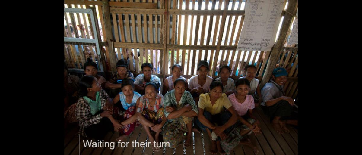 Villagers wait their turn as IOM distributes household kits to survivors of Cyclone Nargis in Kyae Chan Chaung Pyar village, Mawlamyinegyun Township. © IOM/Piers Benatar 2008 - MMM0313