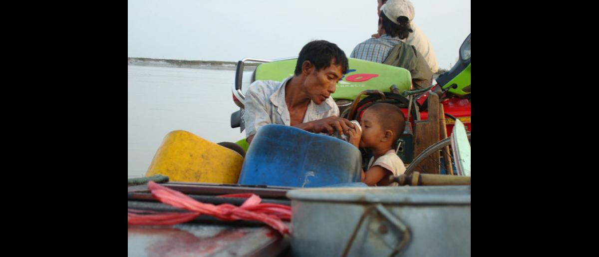 A moment of respite: a father giving his son something to drink as they are sitting on board a ferry. Lack of safe drinking water is a major problems and reports of diarrhoea are increasing. The Myanmar Red Cross Society, supported by the International Federation, is distributing water purification tablets. © International Federation of Red Cross and Red Crescent Societies