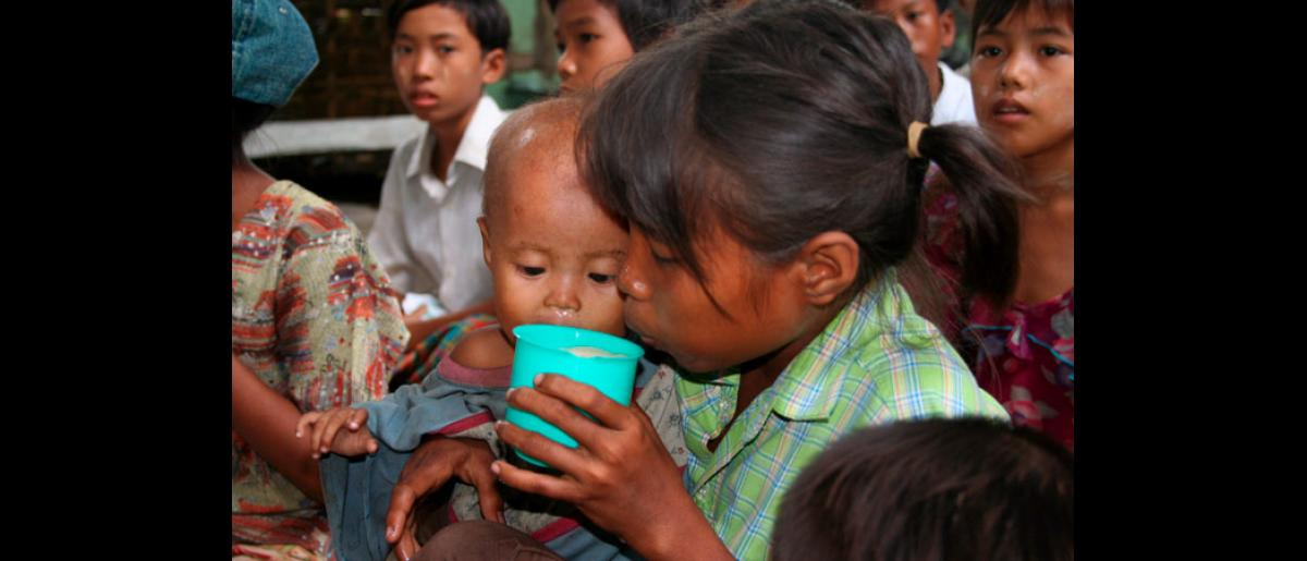 A child drinks powdered milk donated locally to Myanmar Red Cross in Bogale. More than a week after the cyclone struck, hundreds of thousands are still without access to food, water and medicine, threatening a 'health catastrophe' that could increase the death toll 15-fold, aid agencies have warned. © International Federation of Red Cross and Red Crescent Societies