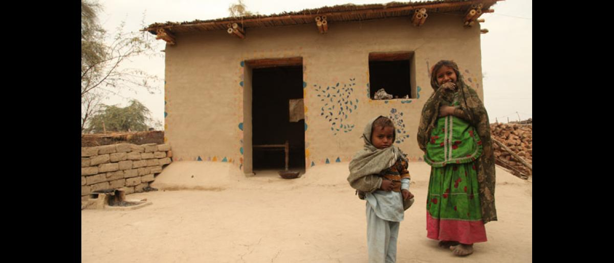 Children standing outside their newly constructed one room shelter. © IOM 2012