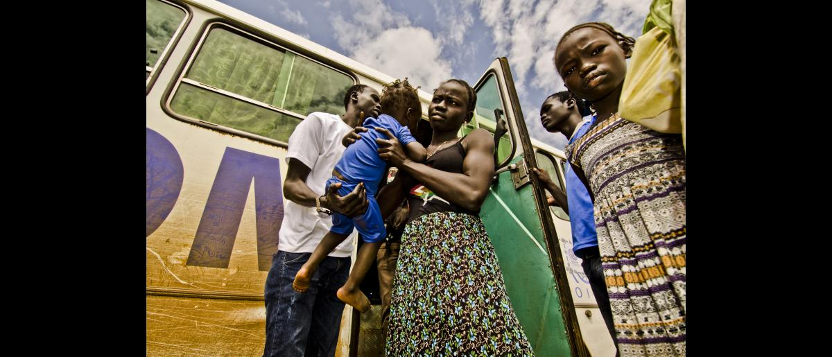 South Sudanese mother and child get off bus during stop over from Pagak Reception Center to Metu Way Station. Day one of three-day convoy of South Sudanese refugees from Pagak Reception Center, Gambella Region to Gure-Shembola in Assosa Region.