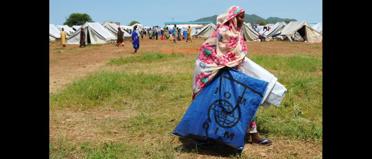 Donna, who recently arrived to the Returnee Transit site in Juba, carries nfis and plastic sheeting to her temporary shelter. IOM and partners provided larger communal tents and smaller, family-sized tents for returnees to the site. © IOM 2012