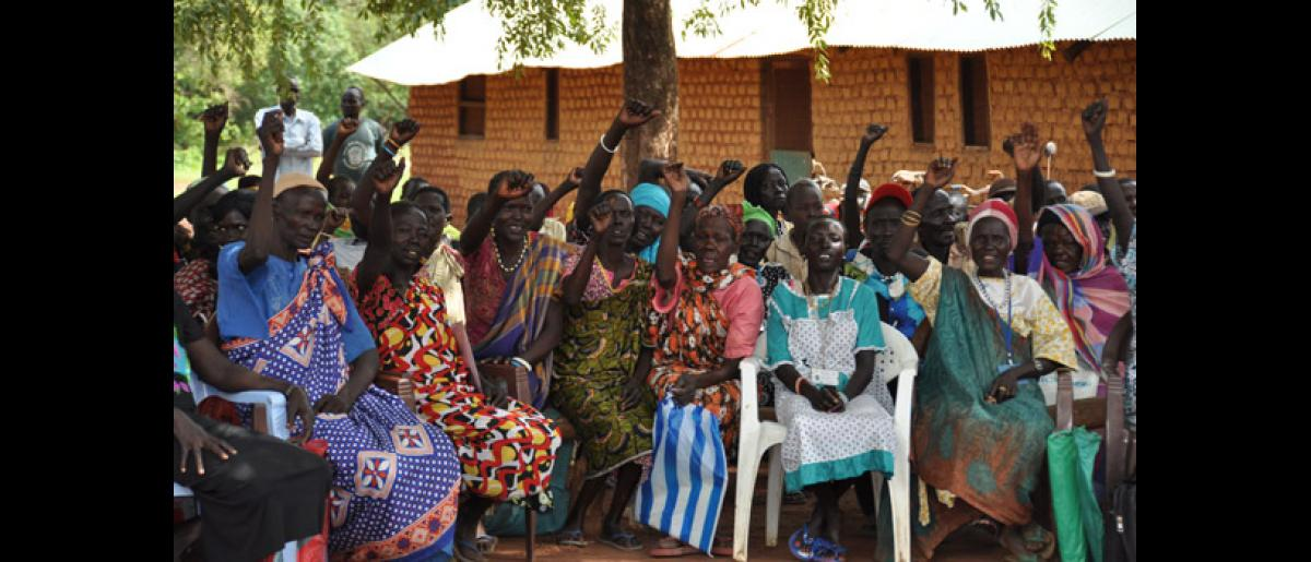 "Female ex-combatants raise their hands in solidarity as they shout, ""South Sudan Oye! South Sudan Oye!"" DDR Day in Mapel, June 2012. © IOM 2012"