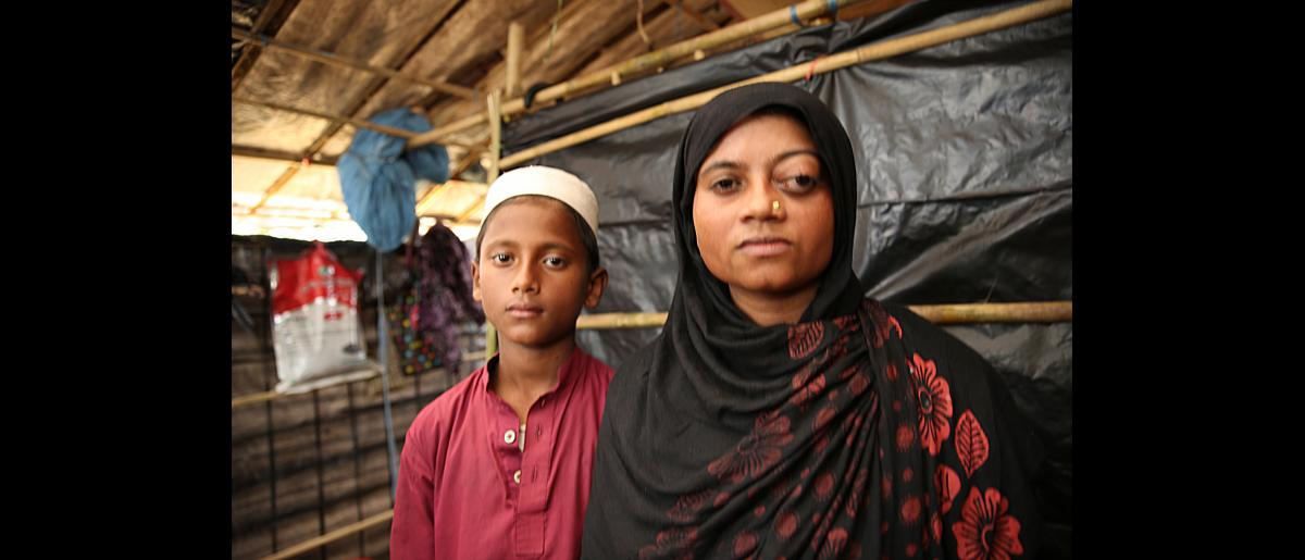 A woman and her son stand in their shelter after receiving an IOM shelter kit in Kutupalong Rohingya refugee settlement, Cox's Bazar, Bangladesh.
