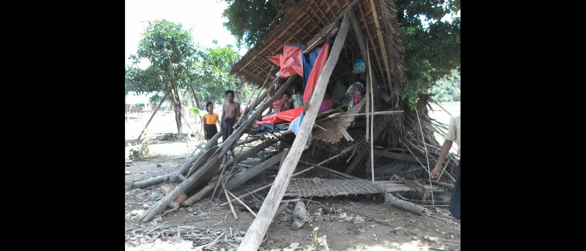 A family sheltering in a collapsed house destroyed by the flood in Rakhine State (11 Aug). © IOM 2015