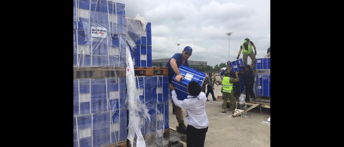IOM staff receiving 500 family kits donated by the Australian Department of Foreign Affairs at Yangon International Airport. The kits contains kitchen sets, blankets, mosquito nets and clothing (10 Aug). © IOM 2015