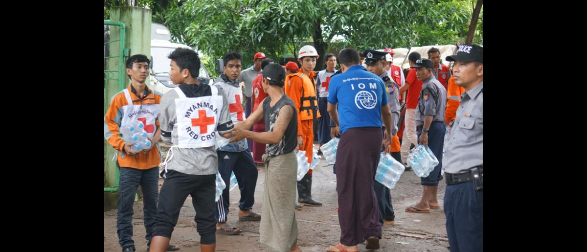 Drinking water and dry noodle packs being distributed to the flood victims in Du Yin Seik Collective Center, Mon State. IOM has distributed 31,800 water bottles, 9,220 dry noodle packs and 7,000 biscuit packs in the state (5 Aug). © IOM 2015