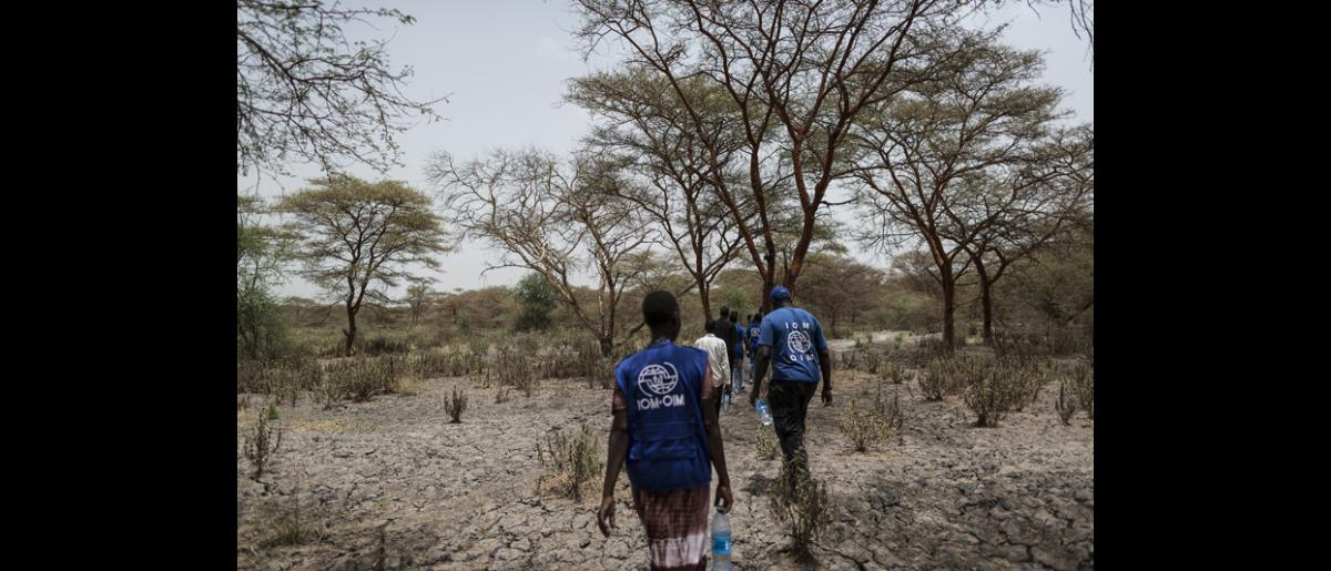 The RRT WASH team travels two hours by foot in one direction to investigate the only water source in Kandak. The team travels back-and-forth for nearly a week to fix a broken borehole. © IOM/Jacob Zocherman 2015