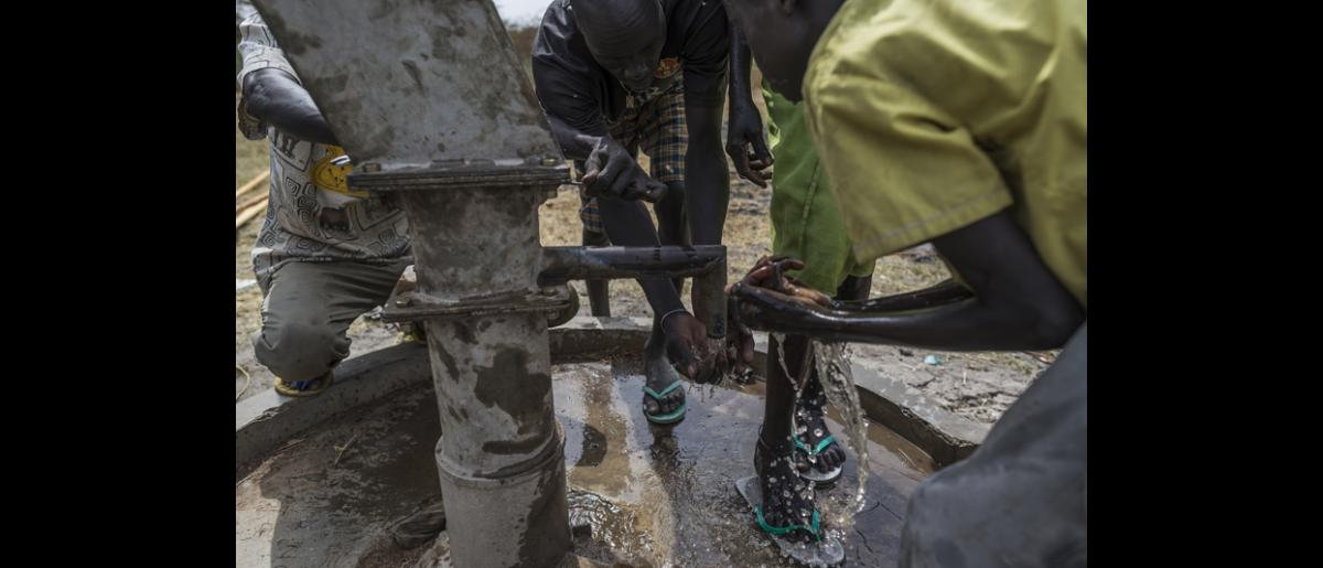 After six days of work trying to repair two boreholes without succeeding, finally Mwangome and his team of local workers manage to repair the third borehole which means the villagers see flowing clean water for the first time in over one year. © IOM/Jacob Zocherman 2015