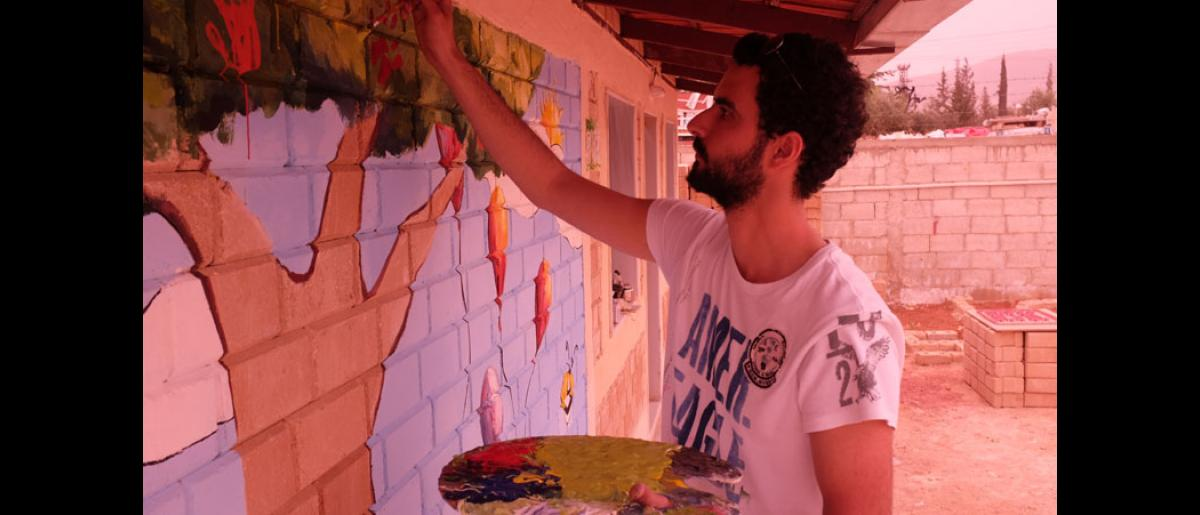 A volunteer artist paints a community built house in Damascus in a project supported by IOM. The houses both help displaced families and ensure social cohesion by providing livelihoods for the displaced. Photo: IOM/Leonard Doyle 2016