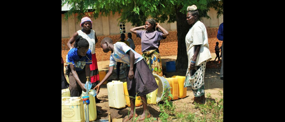 Women from Ambataraku village, Odravu Sub-county at one of the water points. The IOM water system has 22 water stand posts of three taps and five institutional posts. Both the host and refugee communities are benefiting from the WASH interventions. © Abubaker Mayemba / IOM 2018